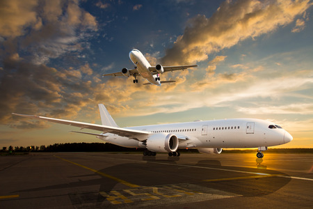 White passenger airplane on airport runway during sunset. And aircraft climb in the sky.