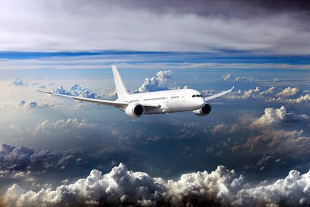 Civil wide-body plane in the sky. Aircraft flying on a high altitude above the storm clouds. 免版税图像