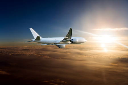 Wide body cargo plane in flight. Aircraft flies high above the clouds towards the sun.