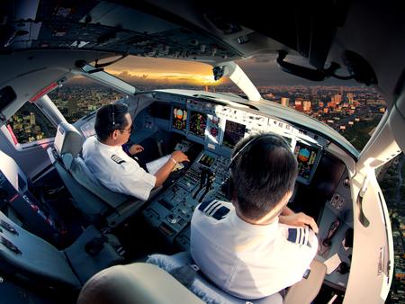 Cabina di pilotaggio di moderni aeromobili passeggeri. Piloti al lavoro. Vista aerea del distretto aziendale moderno della città e del cielo di tramonto. Archivio Fotografico - 94115206