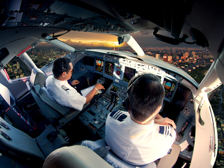 Cockpit of modern passenger jet aircraft. Pilots at work. Aerial view of modern city business district and sunset sky. Standard-Bild