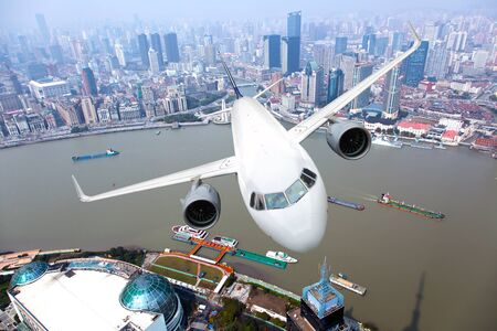 White passenger plane flyes above the buildings, city quarters and river. Front view. 免版税图像