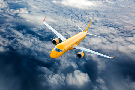 Orange airplane in flight. Passenger plane flying on a high altitude above the clouds. Archivio Fotografico