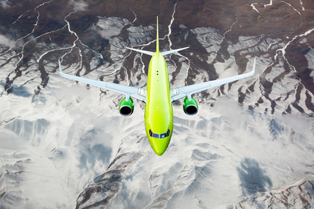 Green passenger plane in flight. Aircraft flies over snow-capped mountain peaks.