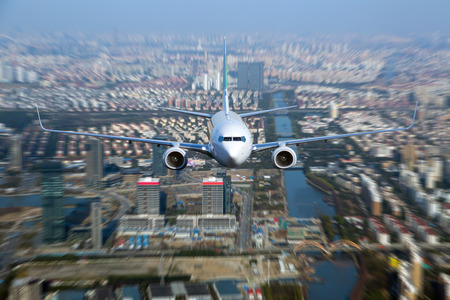 White passenger plane flyes above the buildings, city quarters and river. Front view of aircraft.