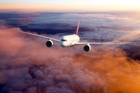 Sunset flight. The passenger wide body aircraft flies high above the colored clouds. Archivio Fotografico