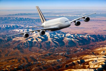 Passenger aircraft in flight. The plane flies over the mountain landscape. Front view of aircraft.
