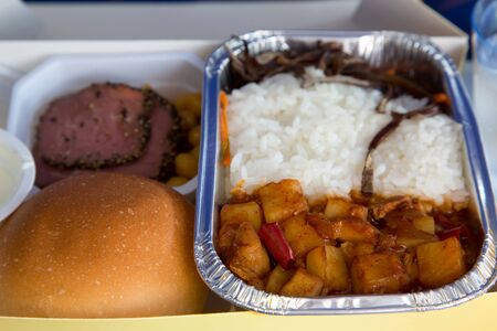 Food served in a passenger aircraft during the flight. Meal on the tray. Salad, meat appetizer, bread bun. Hot dish in the aluminum lunch box: chicken, rice and vegetables.