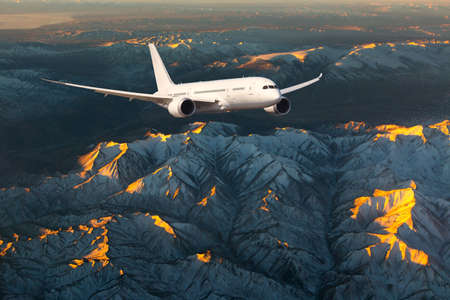 Passenger aircraft in flight. The plane flies over the mountain landscape during the sunset. Front view of aircraft.