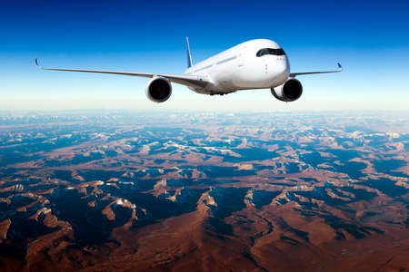 White passenger plane in flight. The plane flies against a background of mountain landscape. Aircraft front view.