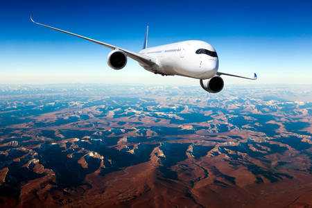White passenger plane in flight. The plane flies against a background of mountain landscape. Aircraft right inclination / front view. 免版税图像