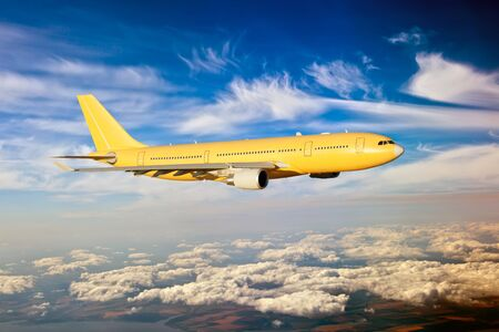 Side view of yellow aircraft in flight. The passenger plane flies high above the clouds. Archivio Fotografico