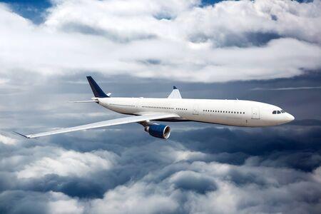 Vista lateral del avión blanco en vuelo. El avión de pasajeros vuela alto entre las capas de nubes.