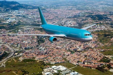 Blue passenger plane in flight. Aircraft  flies over the big city.