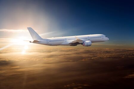 The passenger plane flies over the clouds during sunset. Side view of passenger long range aircraft. 免版税图像