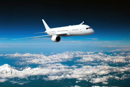 Biały samolot pasażerski w locie. Samolot leci nad pokrytym śniegiem górskim krajobrazem. Widok z przodu samolotu.