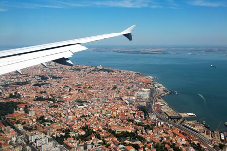 Visit Portugal! The historical center of Lisbon under the plane wing. Roofs of houses and old quarters. 免版税图像