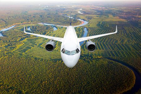 White passenger plane in flight. The plane flies against a background of a forest and river. Aircraft front view.