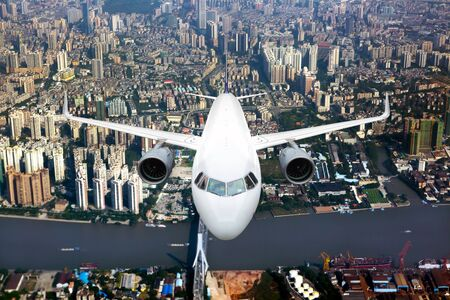 White passenger plane in flight. Aircraft  flies over the skyscrapers of the business center of the big city. Front view of airplane.