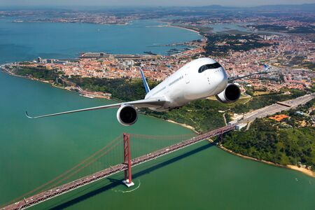 Passenger plane flies above the cable-stayed bridge and river.