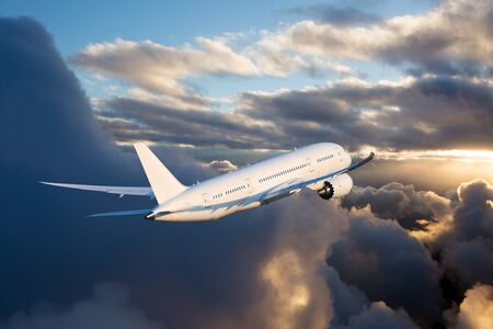 The passenger plane flies away beyond the horizon. The plane flies over the clouds during the sunset. Rear view of aircraft.