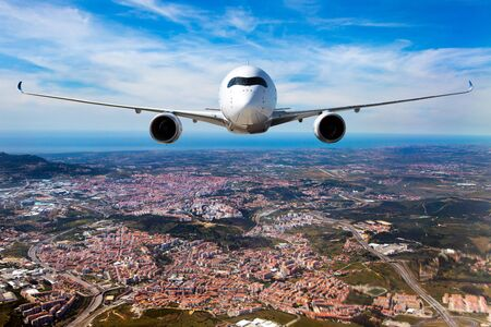 White passenger plane in flight. Aircraft  flies over the big city. Front view of airplane.