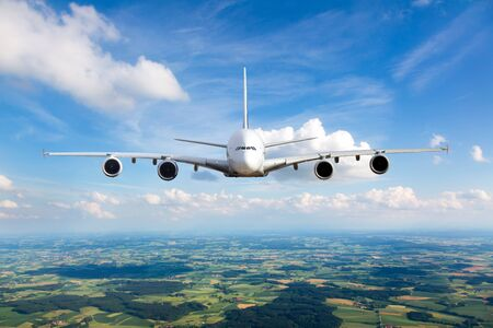 White passenger plane in flight. The plane flies against a background of a endless horizon. Aircraft front view.