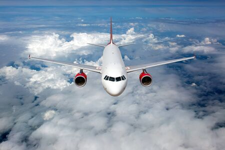 Aircraft in flight. The passenger plane flies high above the clouds. Front view.