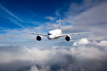 White passenger plane in flight. The plane flies against a background of a cloudy sky. Aircraft front view. 免版税图像