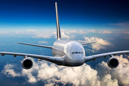 White aircraft in flight. The passenger plane flies high above the clouds and earth. Front view of airplane. 免版税图像