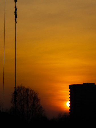 Black silhouette of a multi-storey building against the orange sunset. Building a house against the sun.