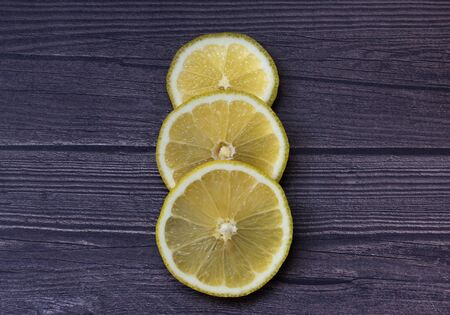 Three yellow lemon slices on a gray wooden background close-up. Juicy fresh fruit. Vegetarian healthy food with vitamins.