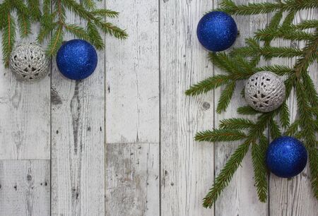Christmas background. Blue and silver Christmas balls with green spruce on grey wooden background. Frame for Christmas text. Top view. Copy space. Stock Photo