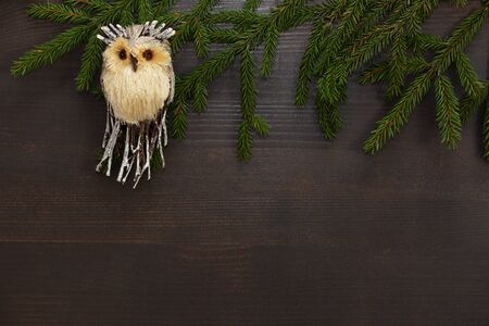 Christmas background. A toy owl with green fir branches on a wooden brown background. Christmas toy.Frame for Christmas text. Top view. Copy space.