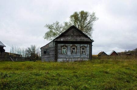 Old wooden house gray in a village in the Ivanovo region in Russia. The house, standing alone on a dull cloudy day in the hinterland of Russia. Foto de archivo - 132105272