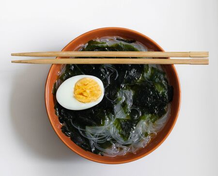Wakame seaweed soup, clear noodles and egg in a round brown plate on a white background. Asian food for vegetarians. A healthy diet