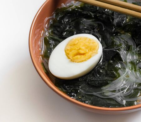 Wakame seaweed soup with noodles and egg in a brown bowl close-up. Traditional Asian food with algae, funchoza and egg. Wholesome food. Reklamní fotografie
