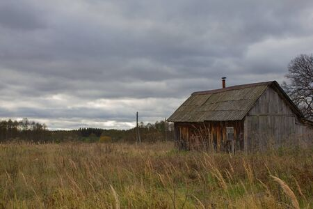 Autumn landscape with an old ruined wooden house. Old house in a field in the village on a cloudy day.