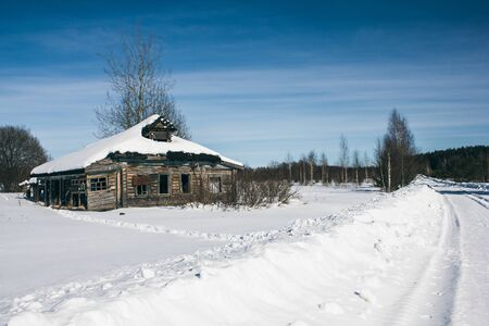 Destroyed wooden house and snow drifts in winter in the village on a frosty Sunny day. Winter landscape. Russian village in winter.
