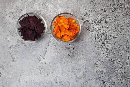 Dried carrot and beet chips in a glass bowl on a gray concrete background. Organic natural food. Top view, flat lay.