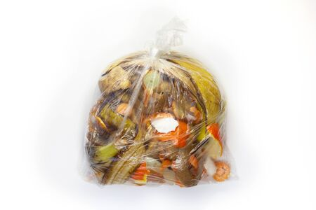Food waste carrots, bananas, potatoes, oranges, onions, eggshells in a transparent bag on a white background.Top view. Flat lay. Waste for recycling. Responsible disposal of household food wastage in an environnmentally friendly way by recycling. Reklamní fotografie
