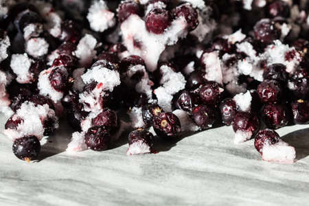 Frozen berries of black currant on a gray background. Storage of frozen food. Frozen product. Black currant in the freeze close-up.