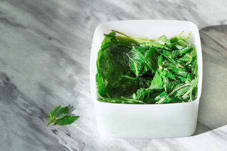 Frozen mint or Melissa. Storage of frozen food. Frozen product. Frozen green leaves of Melissa or mint in a container.
