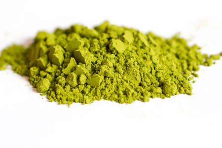 Powdered green matcha tea on a white isolated background close-up. Texture of matcha tea macro background. Copy space. Top view.