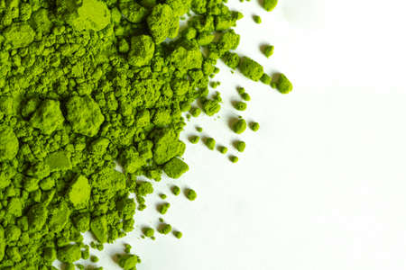Powdered green matcha tea on a white isolated background close-up. Texture of matcha tea macro background. Copy space. Top view. Flat lay.