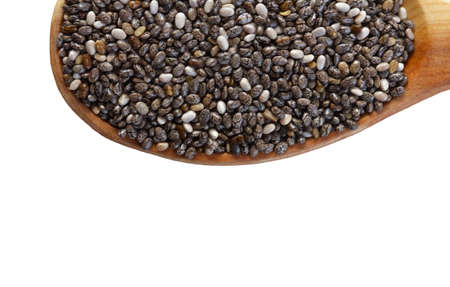 Black Chia seeds in a wooden spoon close-up. Macrophotography of Chia. Health food. Good nutrition. Nutritional Supplement.Top view. 免版税图像
