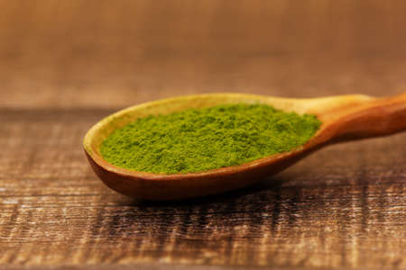 Green tea matcha in a spoon on a brown wooden background close-up. Matcha in a wooden spoon. 免版税图像