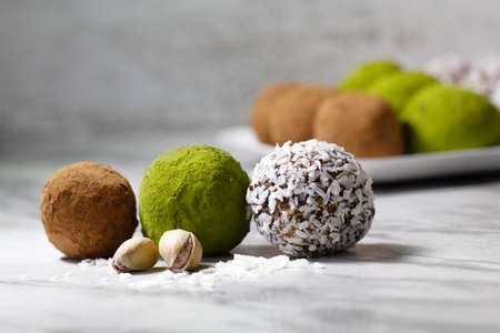Homemade energy balls with dried apricots, raisins, dates, prunes, walnuts, pistachios, green matcha, cacao and coconut. Assortment. Healthy sweet food. Energy balls in a plate on a marble background.
