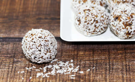 Homemade energy balls with dried apricots, raisins, dates, prunes, walnuts and coconut. Healthy sweet food. Energy balls in a plate on a wooden background. Close up. Side view. Copy space 免版税图像