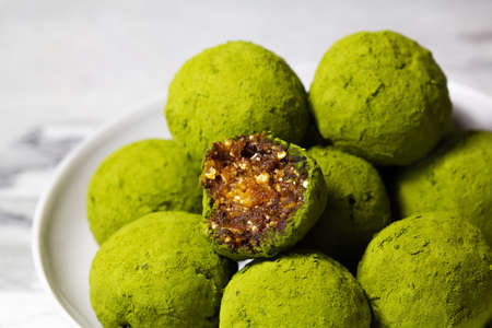 Homemade energy balls with dried apricots, raisins, dates, prunes, walnuts, pistachios and green matcha. Healthy sweet food. Energy balls in a plate on a marble gray background. Close up. Side view.